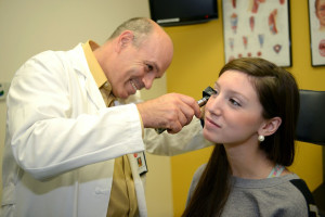 Pediatric ENT specialist examining a patients ear for a blog about determining if cochlear implants are right for your child in Birmingham